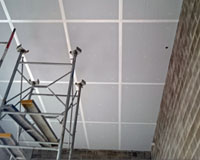 Dow Thermax PIR insulation board direct fixed to cantilevered slab with residence above – white face exposed.
